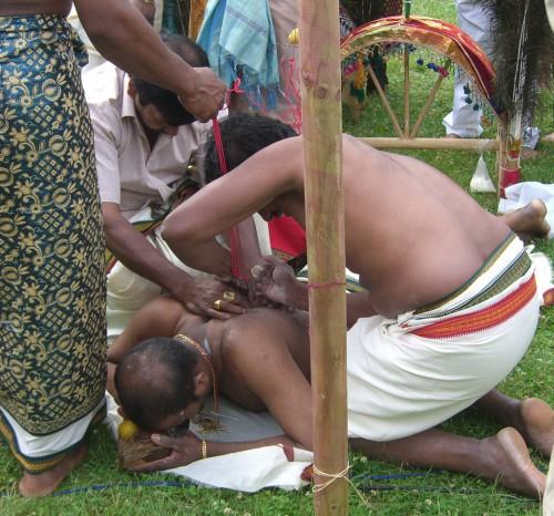 Ein Teilnehmer wird auf den Hakentanz zu Ehren Murukans vorbereitet und hält dabei eine Kokosnuss in den Händen (Foto: mr).