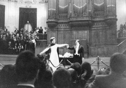 """Beim Schlussapplaus dürfen endlich auch die Zuhörer Bewegung zeigen: Hier bei der Abschiedstourness der Opernsängering Maria Callas in Amsterdam 1973. <a href=""""https://commons.wikimedia.org/wiki/User:FredTC"""">FredTC</a>, <a href=""""https://commons.wikimedia.org/wiki/File:CallasAmsterdam1973a.jpg"""">CallasAmsterdam1973a</a>, <a href=""""https://creativecommons.org/licenses/by-sa/3.0/legalcode"""">CC BY-SA 3.0</a>"""